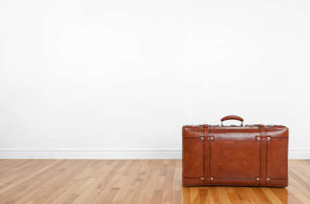 moving in: Vintage leather suitcase on a wooden floor in an empty room  Stock Photo