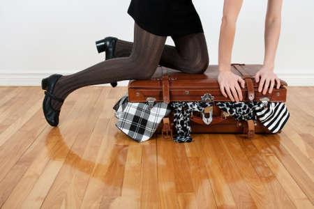 mujer con maleta: Mujer de pie sobre sus rodillas en una maleta demasiado llena con la ropa