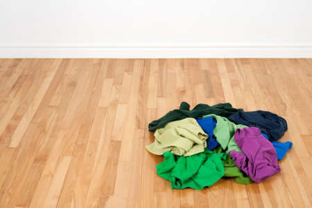 Pile of bright colorful clothes on the wooden floor in empty room. photo