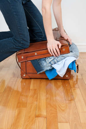 Young woman in jeans trying to close her suitcase with too much clothing.