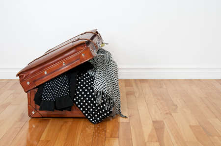 room for text: Black and white polka dot clothes in a retro leather suitcase. Stock Photo