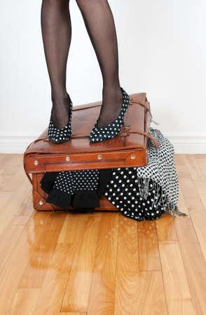 femme valise: Femme en chaussures à talons hauts, debout sur la valise en cuir trop plein avec des vêtements de mode.