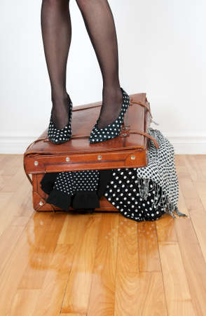 stockings feet: Woman in high heel shoes standing on leather suitcase overfilled with fashion clothing. Stock Photo