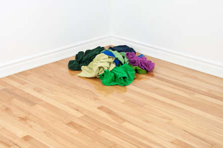 Pile of bright multicolored clothes on the floor in the corner of a room