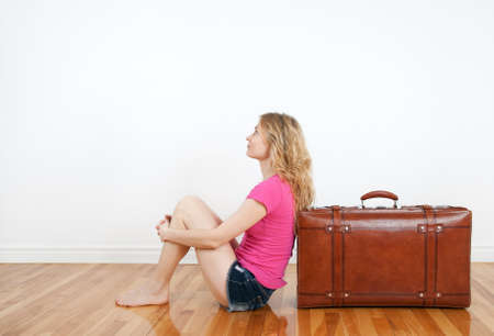 white wood floor: Girl dreaming of vacation, sitting next to a vintage leather suitcase