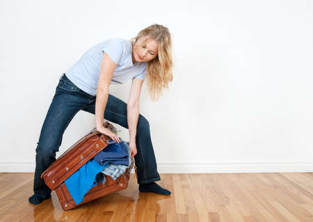 packing suitcase: Young woman tries to close a suitcase with too much clothing in it