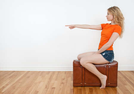 sexy shorts: Young woman sitting on a suitcase and pointing direction where to go   Stock Photo