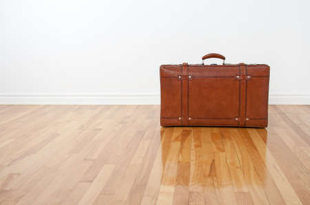 moving out: Retro leather suitcase on the wooden floor in an empty room