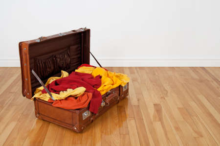 mess: Leather suitcase on the wooden floor, full of orange, red and yellow clothing  Stock Photo