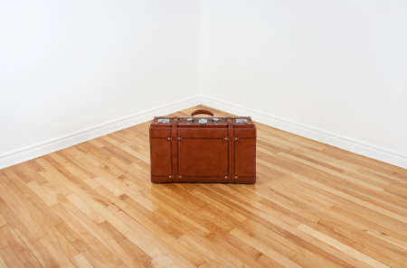 white wood floor: Just arrived or leaving… Vintage leather suitcase in an empty corner of a room  Stock Photo