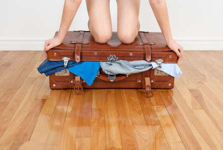 mujer con maleta: Joven mujer de pie sobre sus rodillas en la maleta demasiado llena, tratando de cerrarla