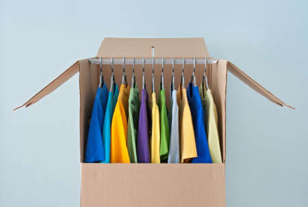 text box: Bright clothing hanging in a wardrobe box, ready for relocation