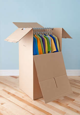 Wardrobe box filled with colorful clothing, prepared for transportation