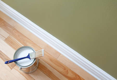 Newly opened can of white paint and paintbrush on wooden floor  photo