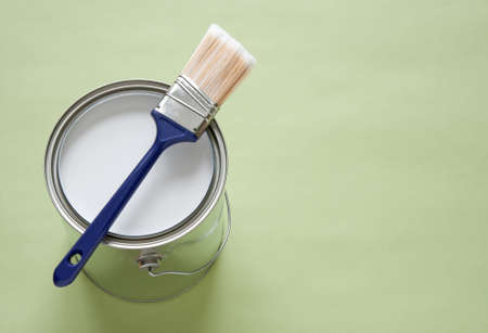 Paintbrush and a newly opened can of white paint on green background