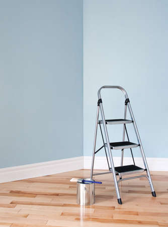 Metal ladder and a can of paint in empty room  Renovation project