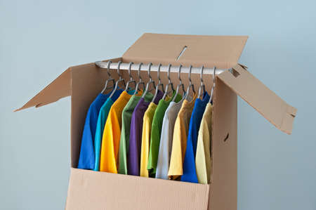 Kleurrijke kleding opknoping in een kast doos, klaar voor het verplaatsen van Stockfoto