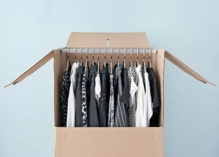 Black and white clothes hanging in a wardrobe box, prepared for moving  photo