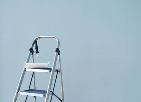 Preparing to paint the wall  Paint roller on a metal ladder   photo