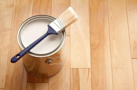 parquet floors: Pennello e una lattina di recente apertura di vernice bianca sul pavimento di legno