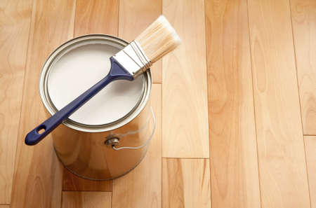 Paintbrush and a newly opened can of white paint on wooden floor