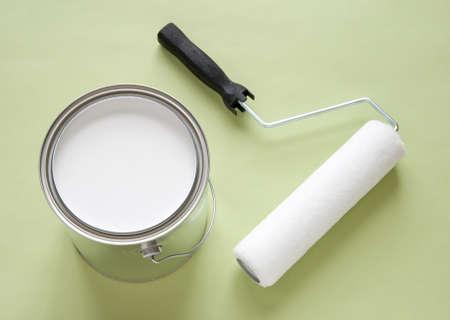 Récemment ouvert pot de peinture blanche et un rouleau sur fond vert