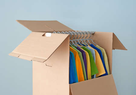 corrugated box: Multicolored clothes hanging in a wardrobe box, prepared for moving  Stock Photo