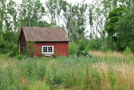 Swedish countryside in summer  Old house painted in traditional red color
