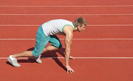 Young man on a racetrack preparing to run  免版税图像