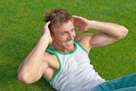 sit ups: Outdoor training  Young man doing sit-ups on green grass  Stock Photo