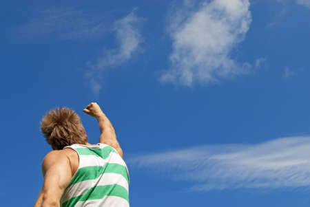 The winner  Sporty guy with his arm raised in joy, on blue sky background  photo