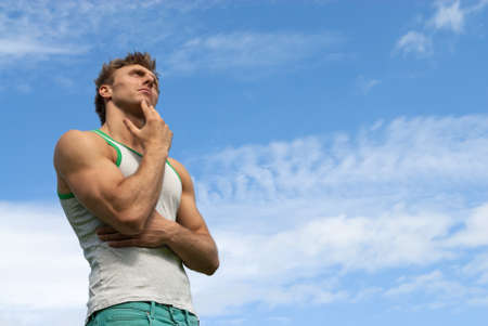 suspicious man: Portrait of a thoughtful strong man, on blue sky background