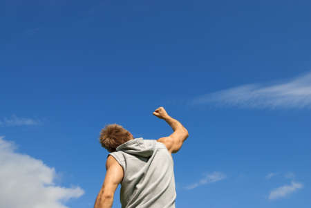 Sporty young man with his arm raised in joy, on blue sky background  photo