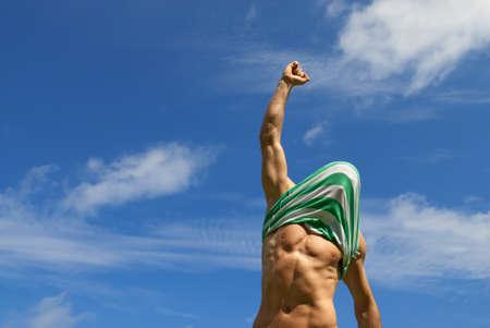 Happy winner with shirt on his head, on blue sky background  Standard-Bild