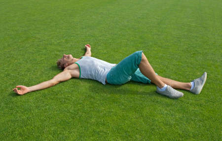 lay: Sporty young man laying on green training field with his arms spread, relaxing  Stock Photo