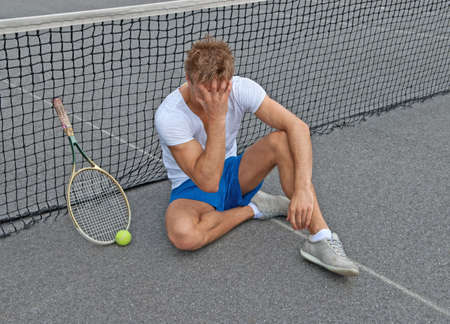 Disappointed tennis player, sitting on the ground, holding his head