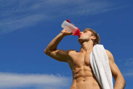 hombres sin camisa: Joven atleta con una toalla blanca sobre su hombro agua potable, Foto de archivo