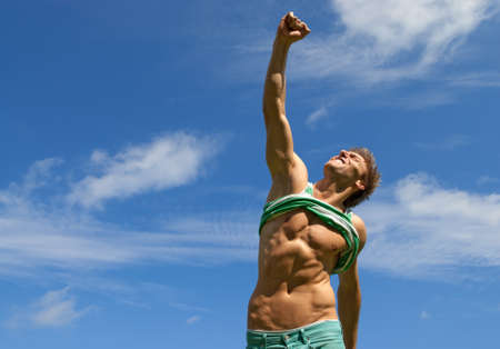 show off: Happy fit man with his arm raised in joy, on blue sky background