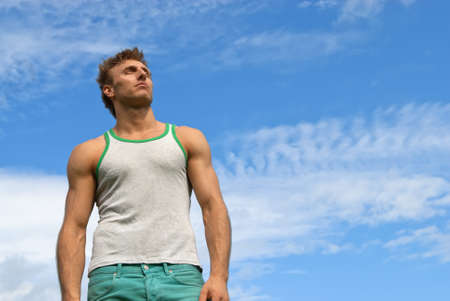 blue sky thinking: Portrait of a strong young man on blue sky background
