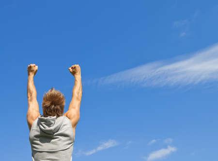 manos levantadas al cielo: Tipo deportiva con los brazos en alto en la alegría, en el fondo del cielo azul