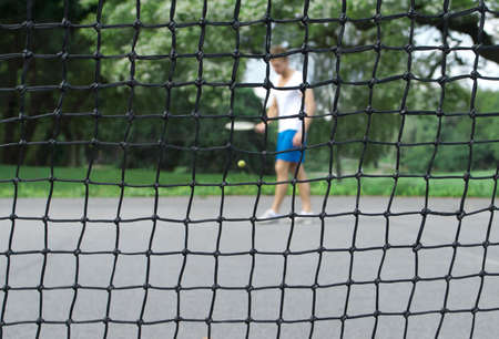 Tennis player with racket and ball seen through the tennis net  Focus on the net  photo