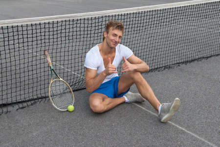 sitting on the ground: Tennis player sitting besides the net and showing thumbs up  Stock Photo