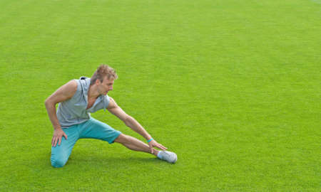 Fit young man exercising outdoors on green sports field  photo