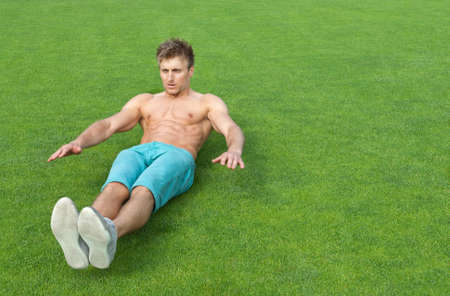 shirtless guy: Young man training outdoors and doing sit-ups on green sports field