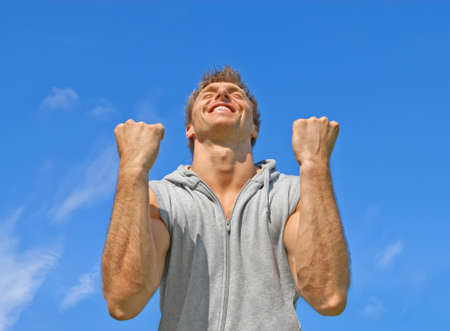 The winner  Happy energetic young man on blue sky background  photo
