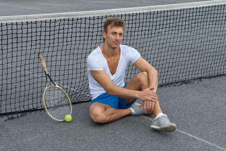 sitting on the ground: Tennis player sitting besides the net on outdoor tennis court