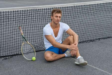 Tennis speler die naast het net op onoverdekte tennisbaan Stockfoto