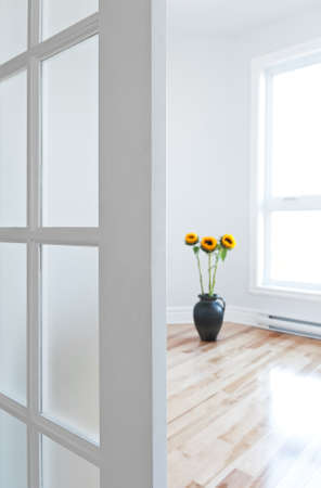 view of a wooden doorway: Opened door leading into a contemporary room full of light, decorated with flowers  Stock Photo