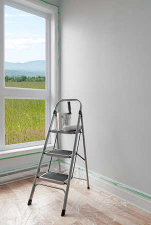 Renovations  Ladder and a can of paint in a room with beautiful view  photo
