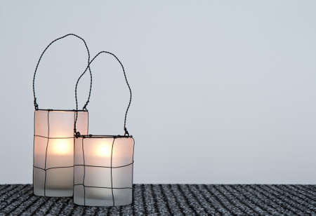 space for copy: Two cozy lanterns made of glass and decorated with metal wire